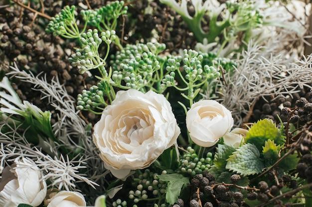 Nahaufnahme des kunstblumenstraußes arrangieren für dekoration in haus, grüne und weiße blume