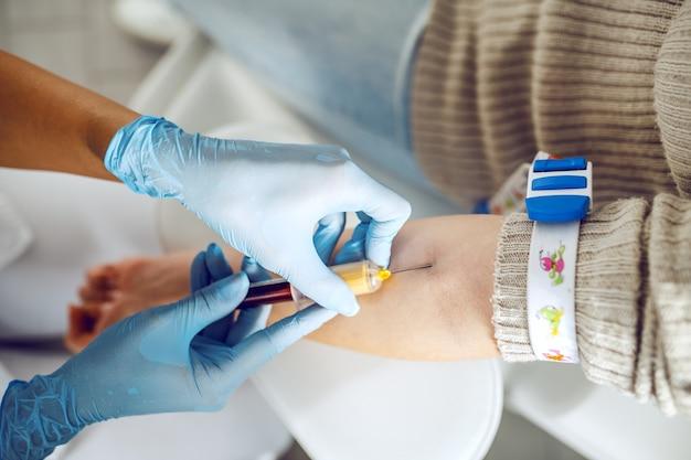 Nahaufnahme des laborassistenten mit sterilen gummihandschuhen, die blutprobe vom patienten entnehmen.