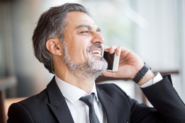 Nahaufnahme des lachenden geschäftsmannes sprechen am telefon