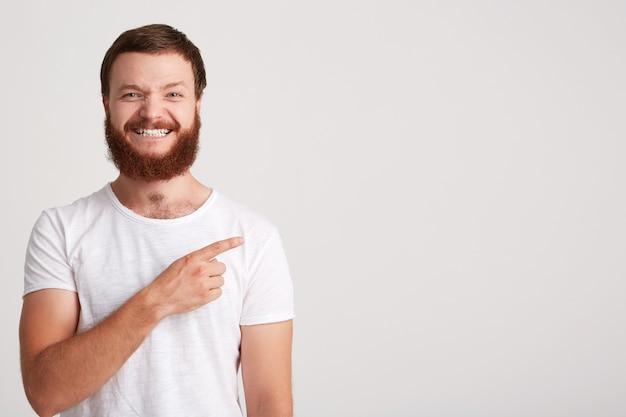 Nahaufnahme des lächelnden attraktiven jungen mannes hipster mit bart trägt t-shirt fühlt sich glücklich und zeigt auf die seite im copyspace mit finger isoliert über weiße wand