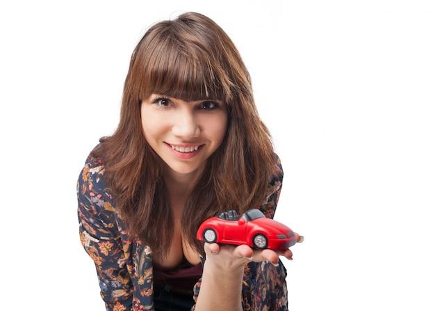 Nahaufnahme des lächelnden mädchen mit einem spielzeugauto zeigt