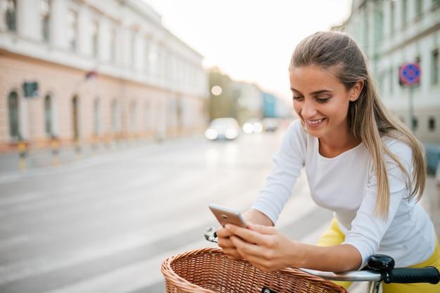 Nahaufnahme des lächelnden mädchens, das telefon beim radfahren in die stadtstraße verwendet.