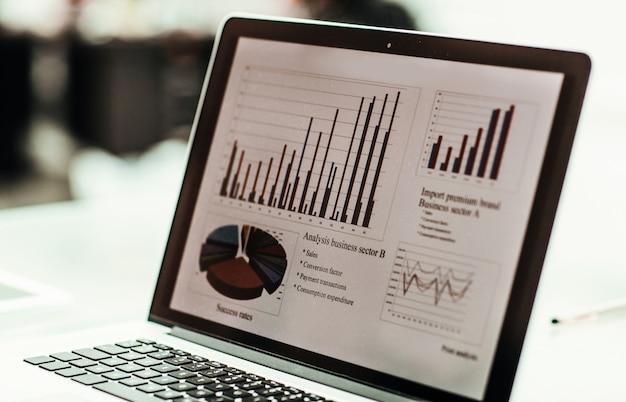 Nahaufnahme des laptopbildschirms mit finanzdiagramm an einem arbeitsplatz des geschäftsmannes