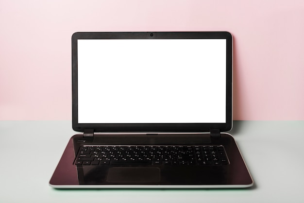 Nahaufnahme des laptops mit weißem schirm auf schreibtisch gegen rosa hintergrund