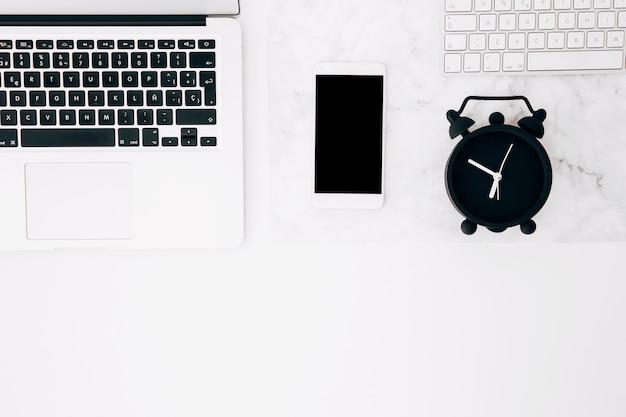 Nahaufnahme des laptops; smartphone; wecker und tastatur auf weißem beschaffenheitsschreibtisch