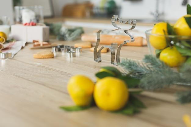 Nahaufnahme des lebkuchenteigs mit mehl und ausstecher auf tisch