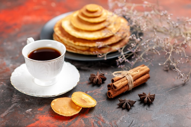 Nahaufnahme des leckeren frühstücks mit plüschigen pfannkuchen und einer tasse tee neben zimtkalk