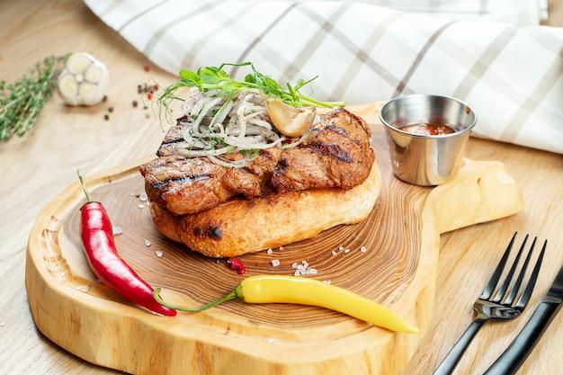 Nahaufnahme des leckeren gegrillten schweinehalses, serviert auf fladenbrot mit zwiebeln, mikrogrün und paprika.