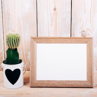 Nahaufnahme des leeren fotorahmens und der saftigen anlage mit heartshape auf topf