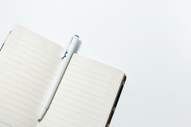 Nahaufnahme des leeren notizbuches und des stiftes, getrennt auf weißem hintergrund.