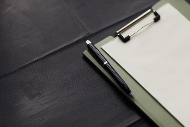 Nahaufnahme des leeren papiers auf der zwischenablage mit stift auf dem holztisch