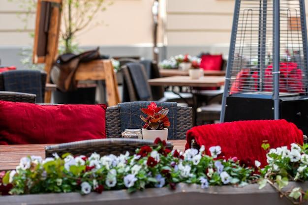 Nahaufnahme des leeren tisches außerhalb des restaurant-cafés auf dem bürgersteig blüht blumenstrauß im blumentopf