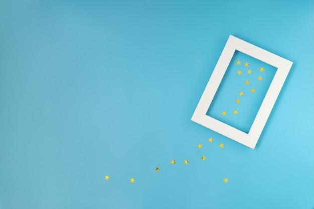Nahaufnahme des leeren weißen rahmens auf blauem hintergrund mit konfetti. weihnachten feiern, neujahr.