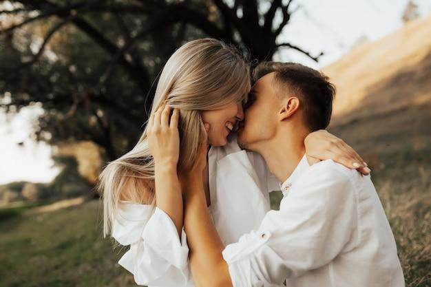 Nahaufnahme des liebenden paares, das einander gegenüber mit geschlossenen augen steht, umarmt und lächelt.