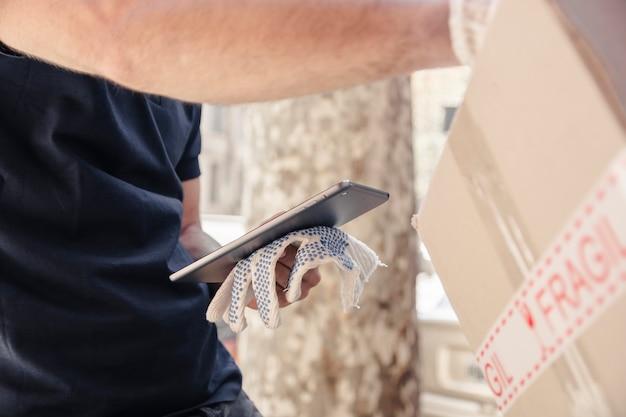 Nahaufnahme des lieferers mit dem paket, das digitale tablette hält