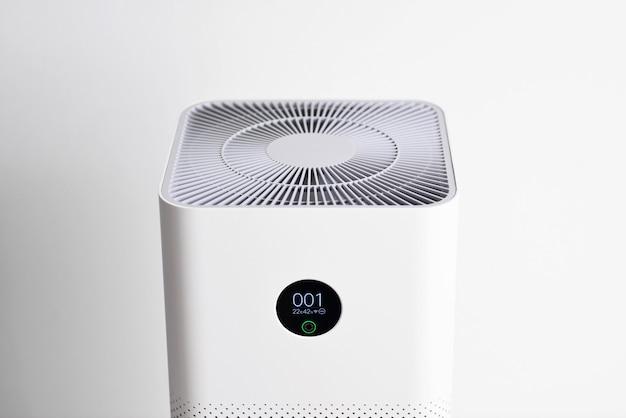 Nahaufnahme des luftreinigers mit monitorbildschirm zeigt die luftqualität im raum pm25-konzept luftreinigersystem, das staub pm25-verschmutzung im wohnzimmer säubert