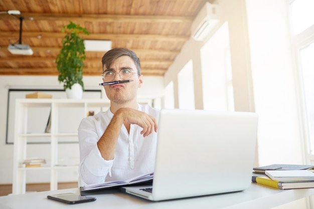 Nahaufnahme des lustigen nachdenklichen jungen geschäftsmannes trägt weißes hemd im büro