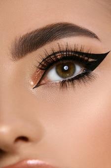 Nahaufnahme des luxusfrauenauges mit schwarzem eyeliner