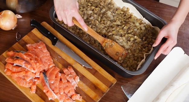 Nahaufnahme des machens der fischtorte mit lachsen und auberginen
