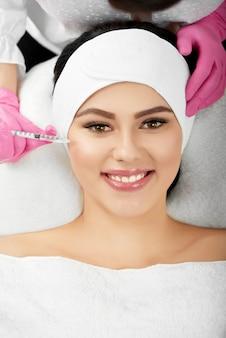Nahaufnahme des mädchens, das während des vergrößerungsprozesses der kosmetologischen lippen liegt