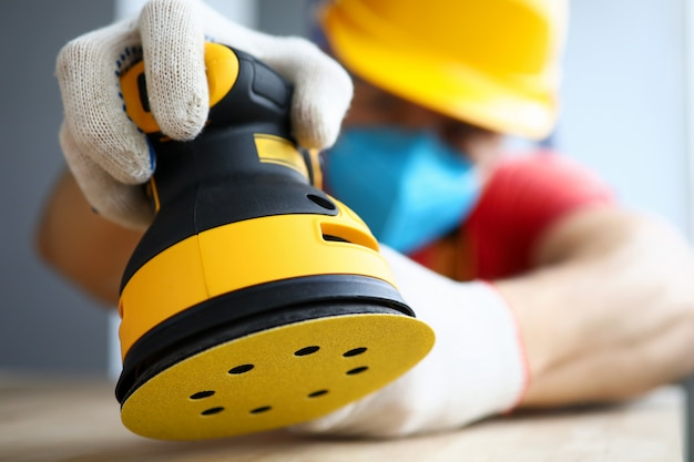 Nahaufnahme des männlichen arbeiters, der stück holz mit moderner elektrischer maschine poliert