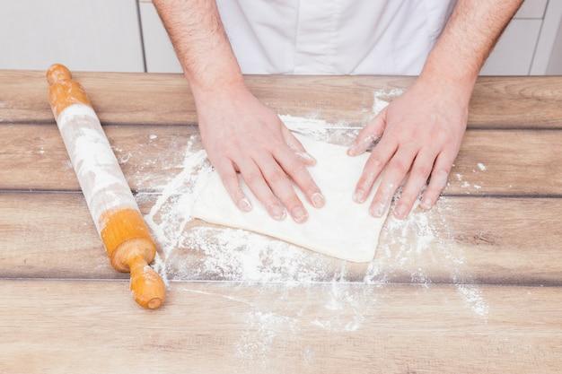 Nahaufnahme des männlichen bäckers den teig auf holztisch vorbereitend