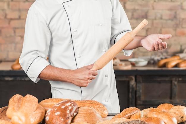 Nahaufnahme des männlichen bäckers stehend hinter der tabelle, die nudelholz hält