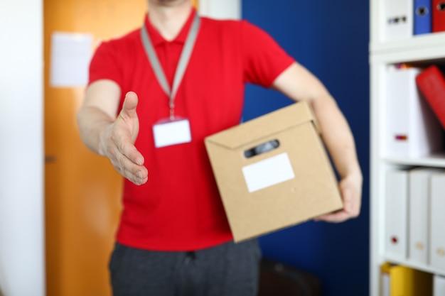 Nahaufnahme des männlichen befreiers, der karton hält und hand schüttelt. mann im leuchtend roten hemd mit namensschild. person, die dem kunden eine box gibt. lieferservice und online-shopping-konzept