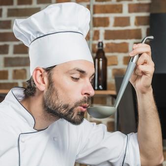 Nahaufnahme des männlichen chefs die suppe vom schöpflöffel riechend