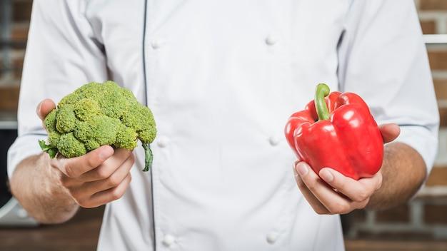 Nahaufnahme des männlichen chefs frischen roten grünen pfeffer und brokkoli halten