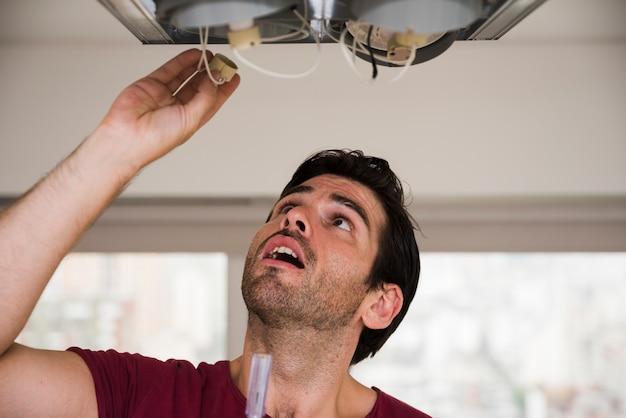 Nahaufnahme des männlichen elektrikers, der halter der deckenleuchte installiert