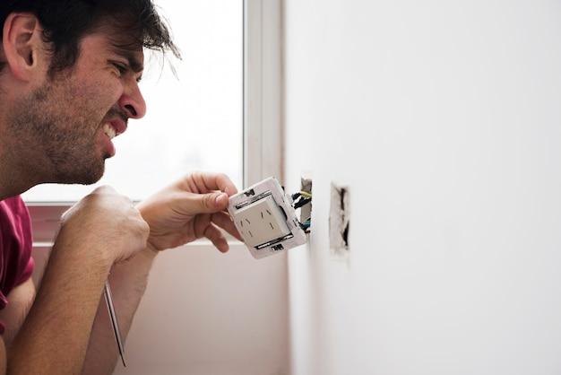 Nahaufnahme des männlichen elektrikers zu hause arbeitend