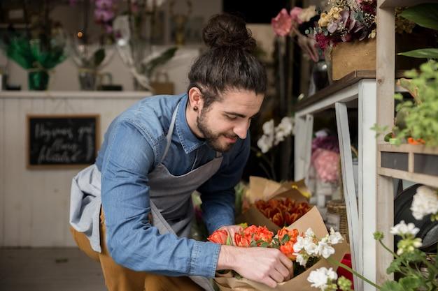 Nahaufnahme des männlichen floristen blumenblumenstrauß im blumenladen schaffend
