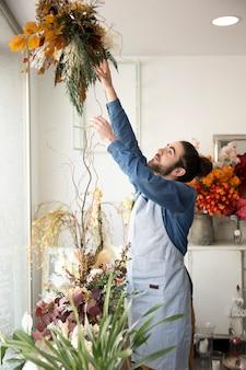 Nahaufnahme des männlichen floristen den blumenstrauß im blumenladen vereinbarend