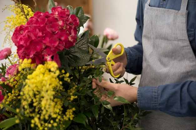 Nahaufnahme des männlichen floristen die blätter des blumenstraußes schneiden