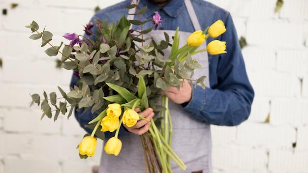 Nahaufnahme des männlichen floristen gelbe tulpen und zweige in der hand halten