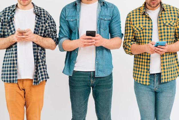 Nahaufnahme des männlichen freunds drei, der intelligentes telefon gegen weißen hintergrund verwendet
