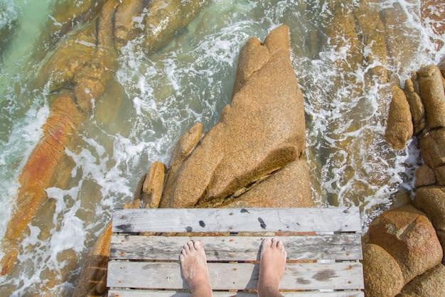 Nahaufnahme des männlichen fußes im blauen wasser am tropischen strand. ferien urlaub.