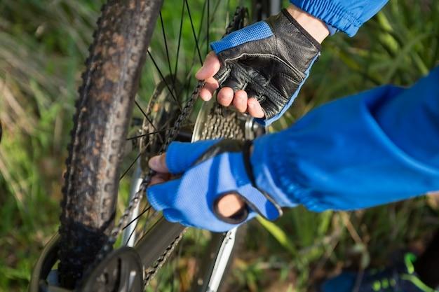 Nahaufnahme des männlichen mannes mountainbiker, der seine fahrradkette repariert