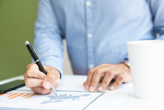 Nahaufnahme des männlichen marketingexperten, der balkendiagramm analysiert