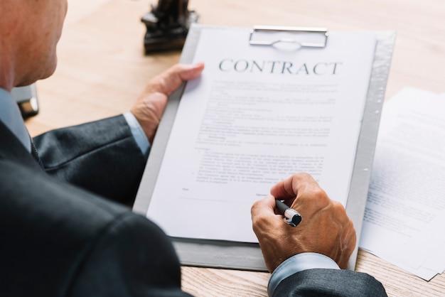 Nahaufnahme des männlichen rechtsanwalts den vertrag auf klemmbrett mit stift unterzeichnend