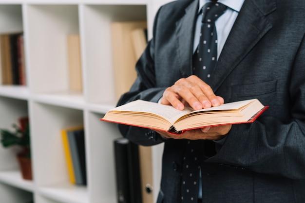 Nahaufnahme des männlichen rechtsanwalts gesetzesbuch halten