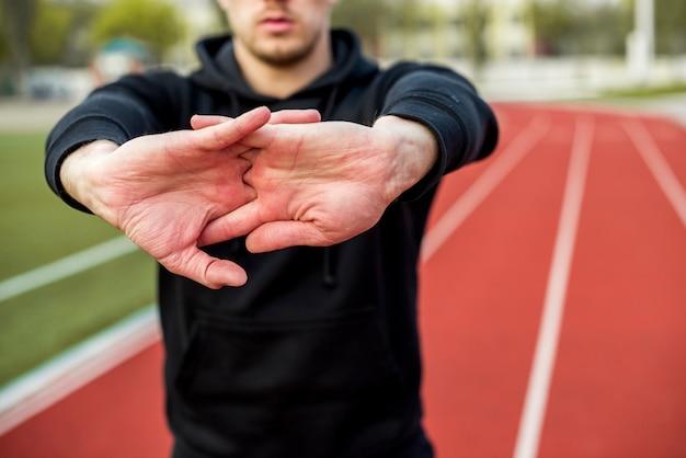 Nahaufnahme des männlichen sportlers seine hände auf rennstrecke ausdehnend