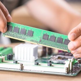 Nahaufnahme des männlichen technikers ram-speicher im motherboard-schlitz installierend