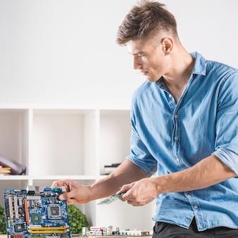 Nahaufnahme des männlichen technikers sitzend auf tabelle, die ram auf modernem motherboard repariert