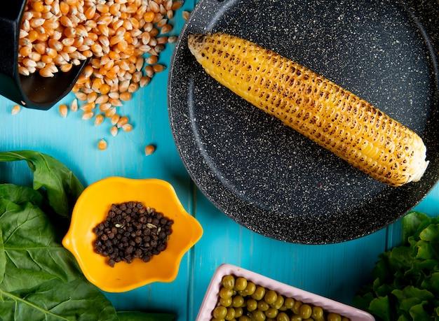 Nahaufnahme des maiskolbens in der pfanne mit schwarzen pfeffersamen und salat des maiskorns auf blauer oberfläche