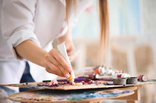 Nahaufnahme des malerpinsels in den frauenhänden, die farben auf palette mischen