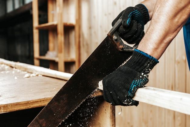 Nahaufnahme des mannbauarbeiters, der block des holzes mit handsäge in werkstatt sägt