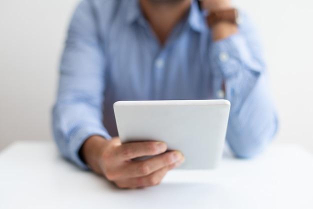 Nahaufnahme des mannes arbeitend, tablette verwendend und um telefon ersuchend