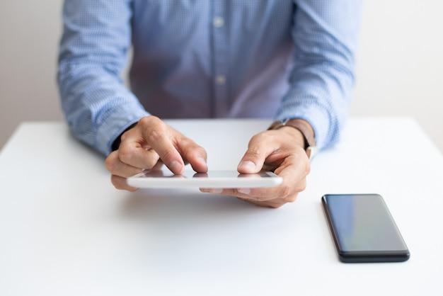 Nahaufnahme des mannes arbeitend und auf tablet-computer klopfend